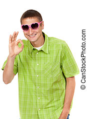 Humorous portrait of a young man in a pink sunglasses, heart-shaped sign shows OK. Studio, isolate on white background.
