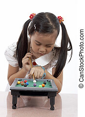 girl playing - young girl playing a toy billiards set
