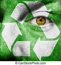 Recycling symbol painted on mans face to raise awareness for...