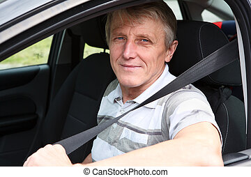 Handsome mature male fastens safety belt sitting in car on...
