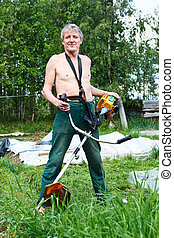Mature Caucasian man a lawn-mower with chopper trimer mowing...