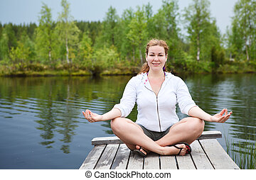 Happy woman in lotos pose sitting on wooden boards on lake...