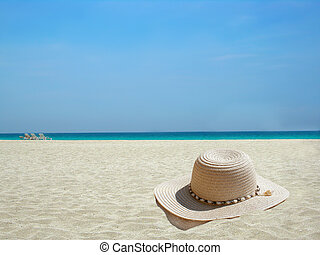 Caribbean beach hat - straw hat on the shore of a Caribbean...
