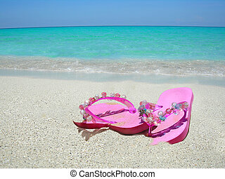 beach sandals - pink sandals on the shoreline of a tropical...