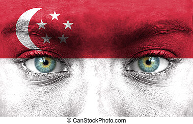 Human face painted with flag of Singapore