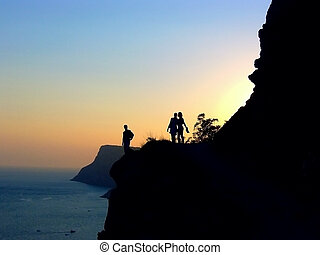 Romantic sunset - Three silhouettes on the cliff against the...