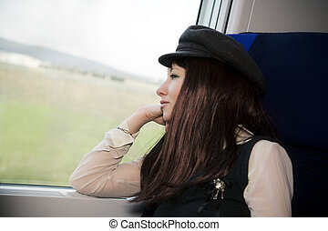 train passenger - nice girl sitting on a train and looking...