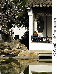 Lonely Woman - Lonely woman in an authentic Asian garden...