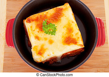 Lasagna dinner in pan on wooden cutting board