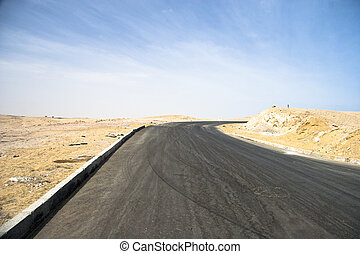 Asphalt road in a desert with cloudy sky on the background