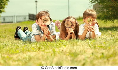 Through magnifying glass - Three cute kids lying on the...