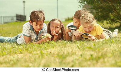 The world around - Children lying on the lawn with...