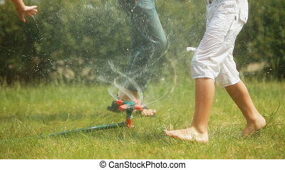 Sprinkler system - Carefree kids playing with sprinkler...