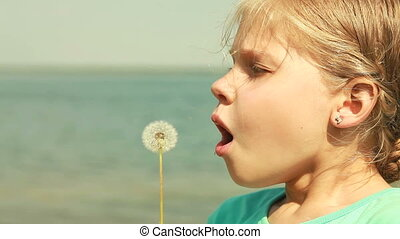 Make a wish - Girl blowing a dandelion off making a wish