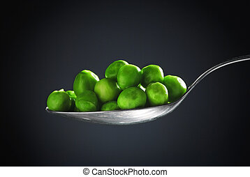 Peas - Spoon full of peas in front of black background