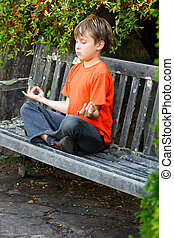 Zen Meditation - A boy sitting cross legged in yoga zen...