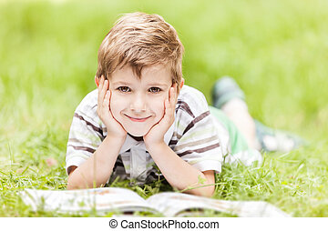 Beauty smiling child boy reading book outdoor on green grass...