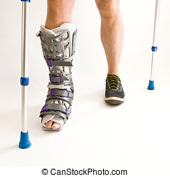Man with a broken leg with Orthotic, walking on crutches