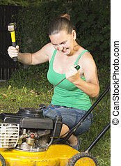 Angry girl breaking in pieces old lawn mover outdoors