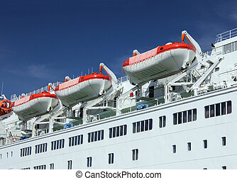 Lifeboats - Three lifeboats on a passenger ship against blue...