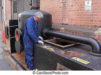 Blowdown vessel - An engineer working on a steam boilerhouse...