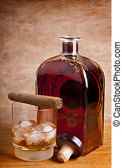 cigar and whiskey - glass and bottle of whiskey with cuban...