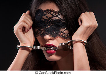 woman in a black mask and metal handcuffs on a dark...