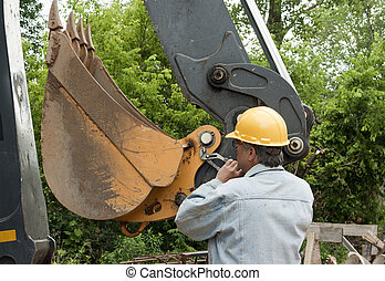 backhoe - man changing a cotter pin on a large backhoe...