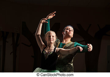 Dance Student Practices with Teacher - Young ballet student...