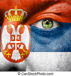 Flag painted on face with green eye to show Serbia support