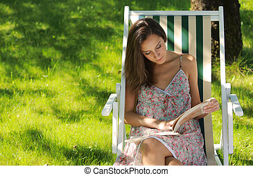 Leisure time - Young woman reading a book at park