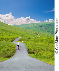 male cyclist riding on road - male cyclist riding up a hill...
