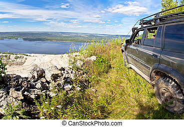 All-wheel drive SUV on the edge of a cliff in a quarry rubble. Against the background of blue sky.