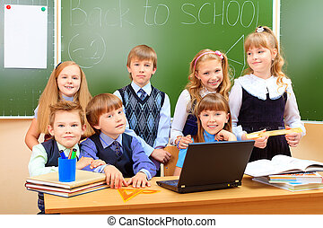 technology - Happy schoolchildren at a classroom during the...