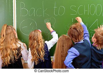 blackboard - Group of schoolchildren writing on a blackboard...