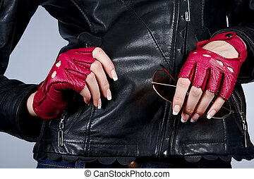 Women's hands with the sunglasses in stylish gloves -...