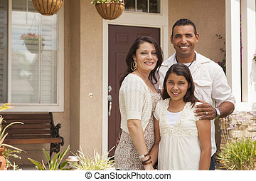 Small Hispanic Family in Front of Their Home - Hispanic...