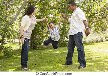 Hispanic Mother and Father Swinging Son in the Park