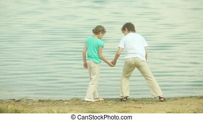 Skipping stones together - Kids on the beach of the lake...