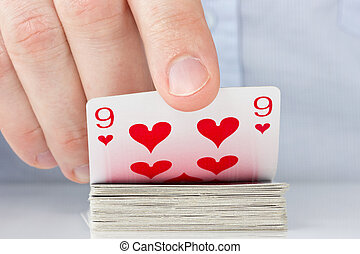 hand revealing nine of hearts - Gamble concept . Player hand...