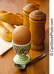 breakfast egg with salt, pepper and bread on a wooden...