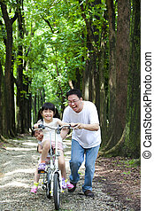 Father Teaching daughter  to riding bicycle