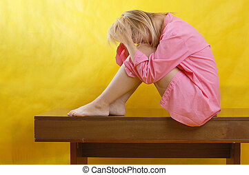 depressed woman sitting on the table, yellow background