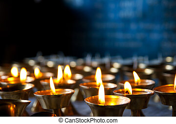 Burning candles in sconces on black blue background