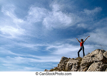 A young girl stands on the edge of a cliff with a beautiful...