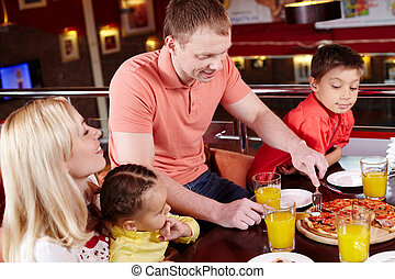 At pizzeria - Family gathered together to enjoy pizza at the...