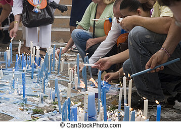 Devotees lighting candles - Low angle cropped shot of...