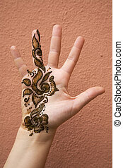 Henna on hand - Henna applied on hand against a backdrop of...