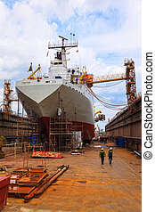 A ship in a dry dock - A large cargo ship is being renovated...