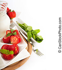 Strawberry with a mint and jug of milk on a white serviette